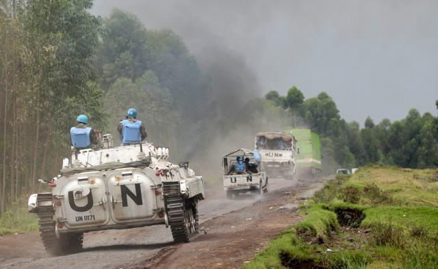 U.N. peacekeepers drive tank as they patrol past deserted Kibati village