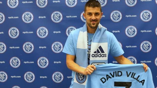 15 David Villa on the NYCFC backdrop holding named shirt4